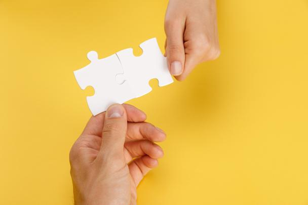 cropped view of man and woman holding pieces of white puzzle on yellow background - Photo, Image