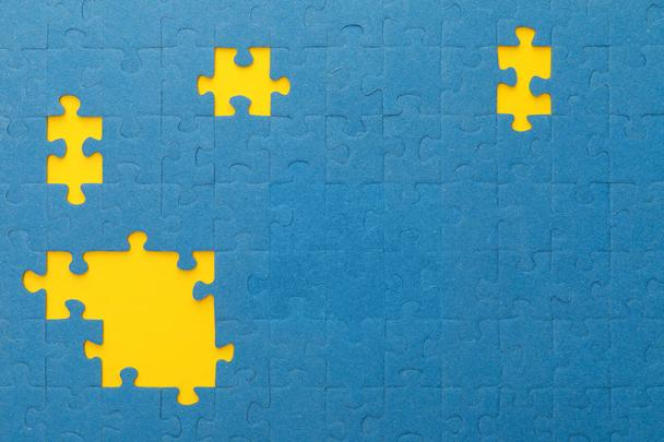top view of blue jigsaw puzzle with yellow gaps - Photo, Image