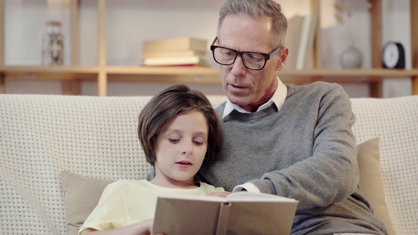 grandpa and grandson reading book together in living room - Footage, Video