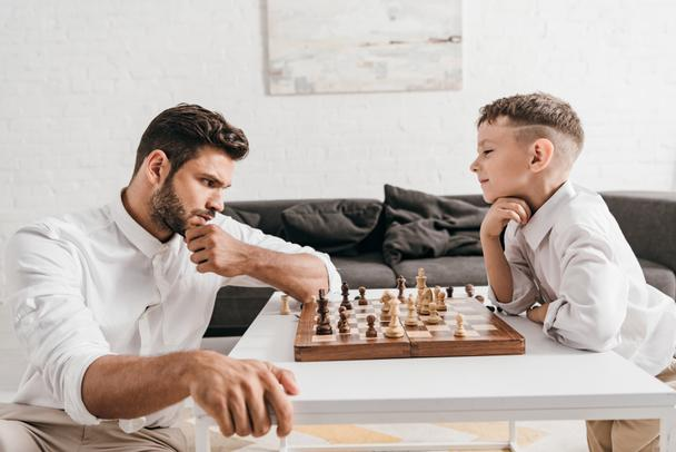 dad and son playing chess together at home - Photo, Image