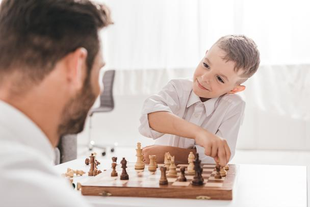 selective focus of dad and son playing chess together at home - Photo, Image