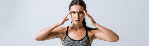 panoramic shot of sportswoman with headache touching temples isolated on grey - Photo, Image