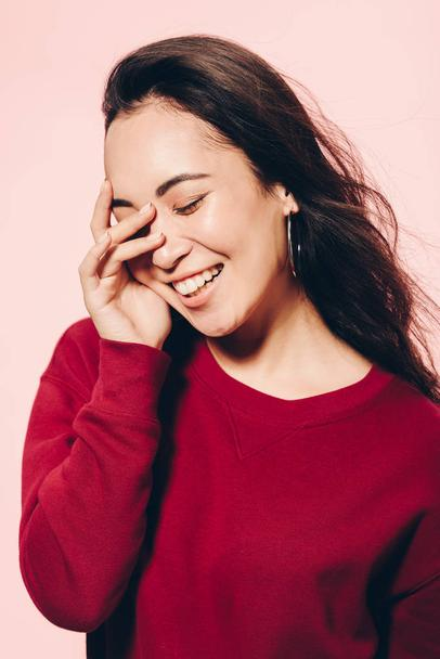 attractive asian woman with closed eyes in red sweater smiling isolated on pink  - Photo, Image