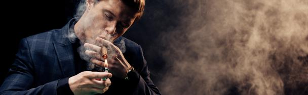 panoramic shot of handsome man holding lighter while smoking on black with smoke  - Photo, Image