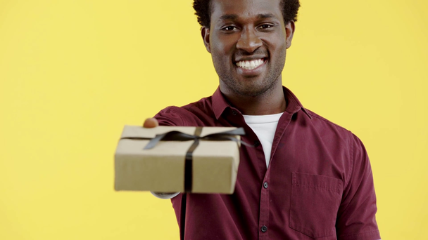 handsome african american man presenting gift box isolated on yellow - Footage, Video