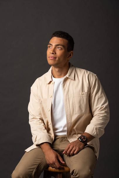 thoughtful handsome mixed race man in beige shirt looking away on black background - Photo, Image