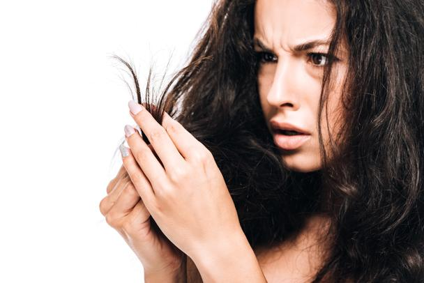 stressed brunette woman looking at damaged dry hair isolated on white - Photo, Image