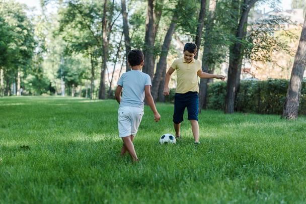 happy multicultural boys playing football on green grass  - Photo, Image