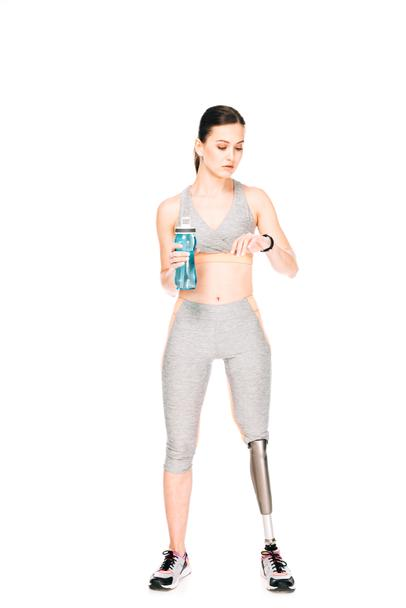 full length view of sportswoman with prosthetic leg holding sport bottle and looking at smartwatch isolated on white - Photo, Image
