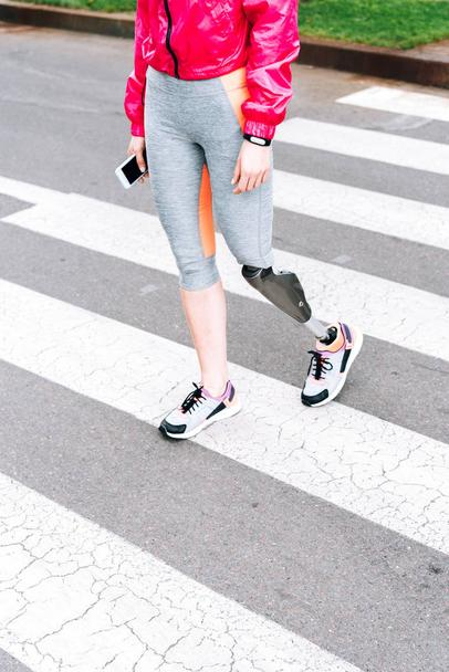 partial view of disabled sportswoman with prosthesis holding smartphone on street - Photo, Image