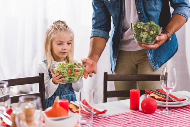 cropped view of father giving bowl with salad to cute daughter in Thanksgiving day  - Photo, Image