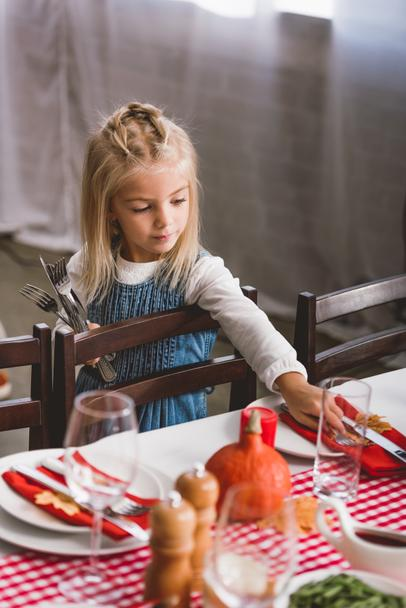 selective focus of cute kid smiling and putting on table cutlery in Thanksgiving day   - Photo, Image