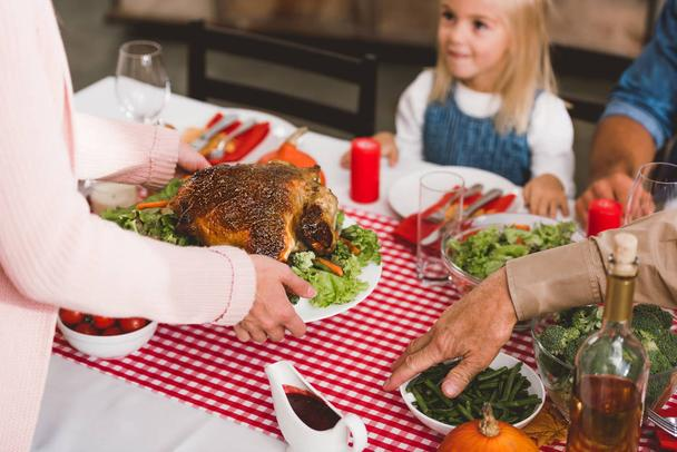 cropped view of mother holding plate with turkey in Thanksgiving day    - Photo, Image