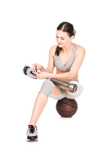 smiling disabled sportswoman with prosthesis sitting on basketball ball and tying shoelaces isolated on white - Photo, Image