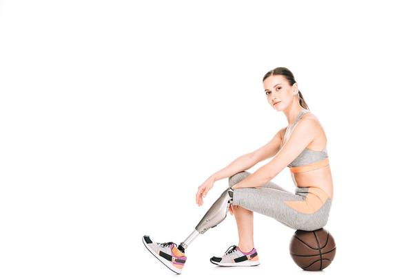 disabled sportswoman sitting on basketball ball isolated on white - Photo, Image