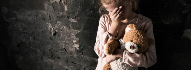 panoramic shot of upset kid touching face while holding teddy bear in dirty room, post apocalyptic concept - Photo, Image