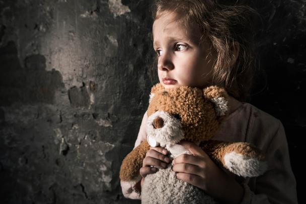 upset kid holding teddy bear in dirty room, post apocalyptic concept - Photo, Image