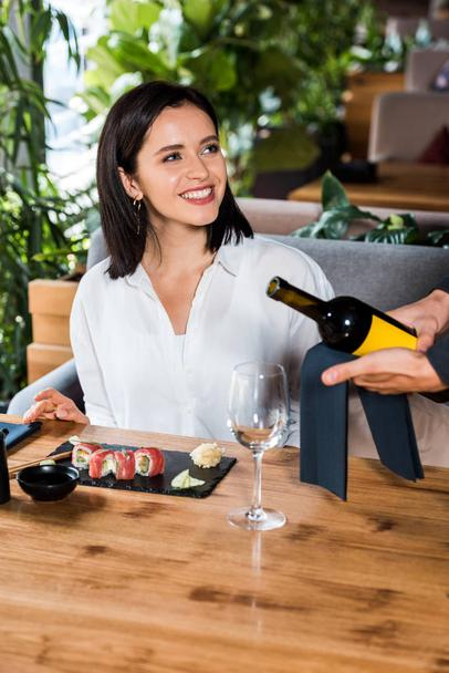 cropped view of waiter holding bottle with wine near glass and happy woman in sushi bar  - Photo, Image