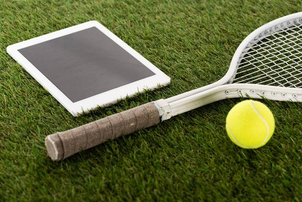 tennis racket and ball near digital tablet with blank screen on green grass, sports betting concept - Photo, Image