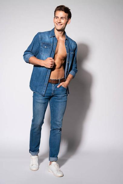 happy man in jeans and denim shirt standing with hand in pocket on white  - Photo, Image