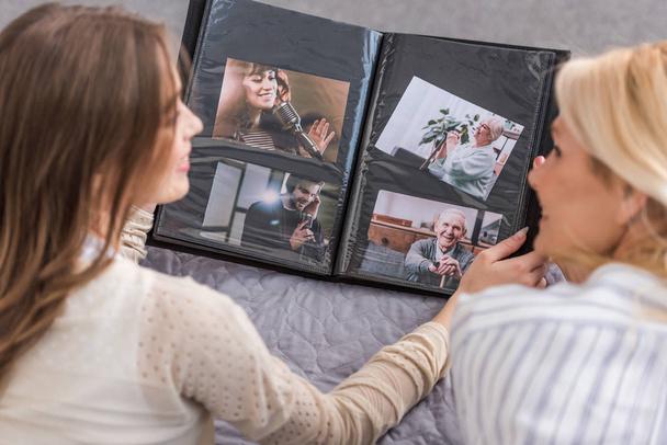 Overhead-Ansicht von Mutter und Tochter im Gespräch, während sie auf dem Bett liegen und das Fotoalbum betrachten - Foto, Bild