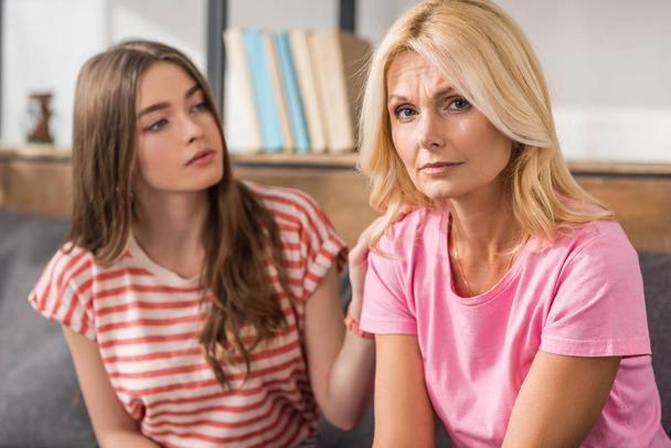 selective focus of upset mature woman looking at camera while sitting near daughter  - Photo, Image