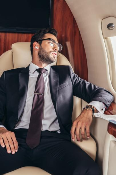 handsome businessman in suit listening music in private plane  - Photo, Image