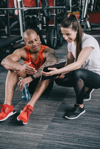 smiling trainer showing clipboard to cheerful african american sportsman sitting on floor - Photo, Image