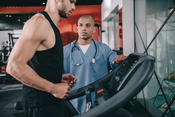 young african ameriican doctor supervising sportsman running on treadmill - Photo, Image