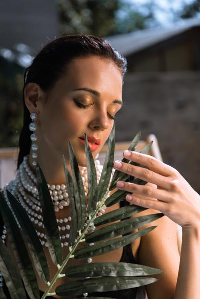 attractive woman in earrings with closed eyes holding plant  - Photo, Image
