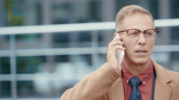 smiling businessman in coat talking on smartphone  - Footage, Video