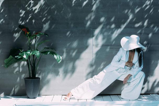 adult woman in white suit and hat posing outside  - Photo, Image