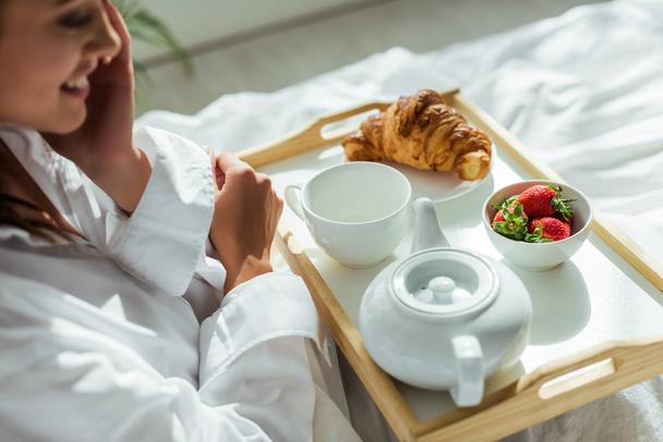 cropped view of woman in white shirt having breakfast in bed at morning  - Photo, Image