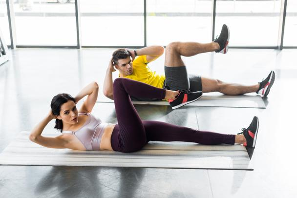 sportsman and sportswoman doing crunches on fitness mats in sports center - Photo, Image
