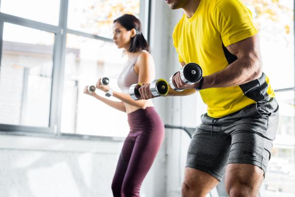 cropped view of sportsman and sportswoman working out with dumbbells in sports center - Photo, Image