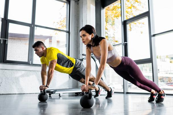 sportsman and sportswoman doing plank on weights in sports center - Photo, Image