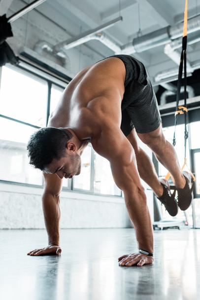 handsome sportsman working out on suspension trainer in sports center  - Photo, Image