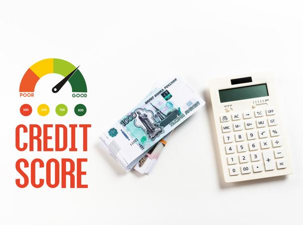 Зверху на калькулятор біля рублів росіян на білому тлі з ілюстрацією про кредит. - Фото, зображення