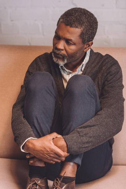 depressed african american man sitting on sofa at home and looking away - Photo, Image
