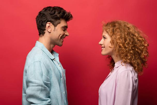 beautiful happy couple in casual clothes looking at each other isolated on red - Photo, Image