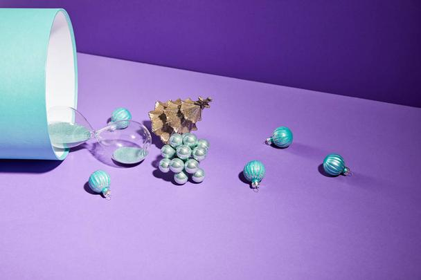 Christmas decoration and hourglass scattered from blue gift box on purple background - Photo, Image