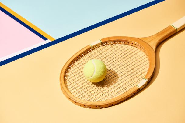 Yellow tennis ball on racket on background with blue lines - Photo, Image