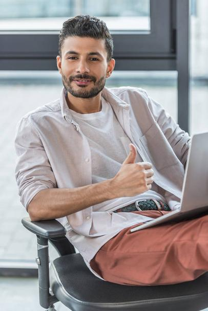 smiling businessman in casual clothes sitting on office chair, showing thumb up and looking at camera - Photo, Image