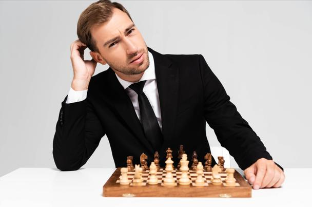 pensive and handsome businessman in suit sitting near chessboard isolated on grey  - Photo, Image