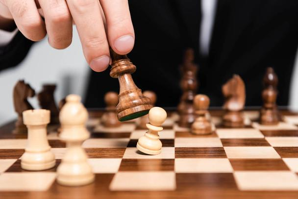 cropped view of businessman holding chess figure above chessboard  - Photo, Image