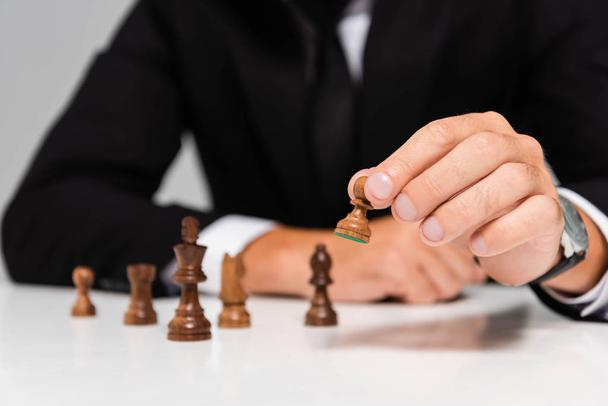 cropped view of businessman in black suit playing chess  - Photo, Image