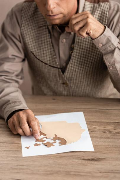 cropped view of senior man holding glasses and matching puzzle pieces  - Photo, Image