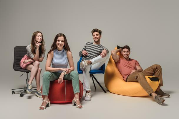 smiling friends sitting on different chairs, on grey - Photo, Image
