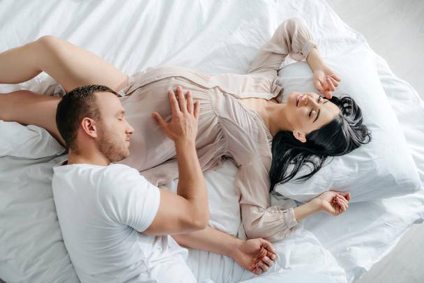 handsome man hugging pregnant woman in bed - Photo, Image