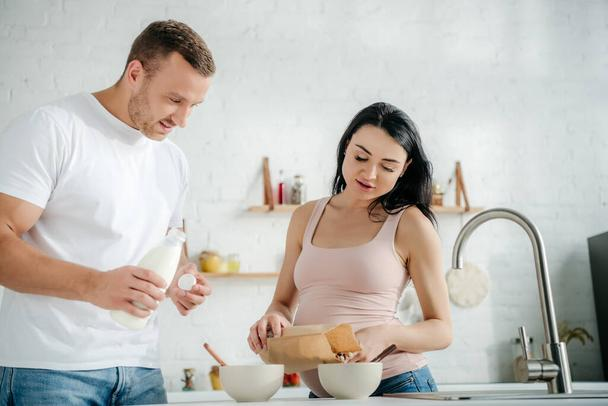 happy pregnant couple making cereals with milk in kitchen - Photo, Image